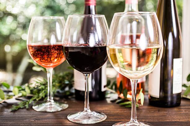 various wine selections, glasses on outdoor dining table. bottles. nobody. - roten küchentische stock-fotos und bilder