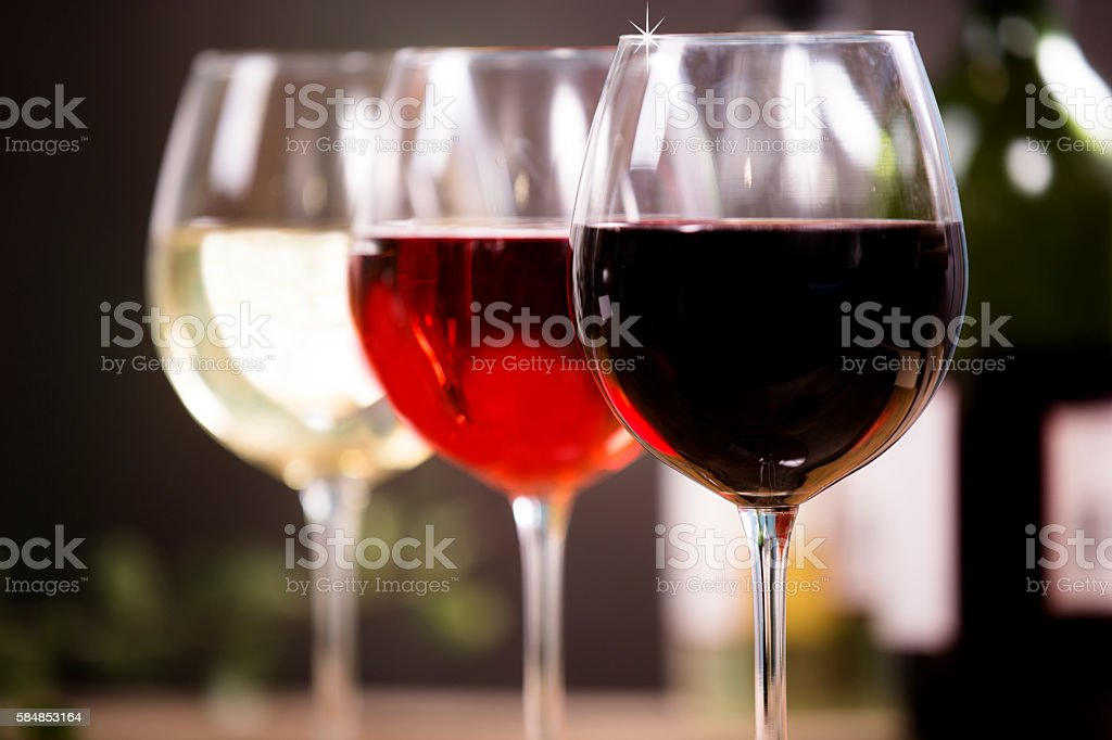 Various wine selections, glasses on rustic dining table. stock photo