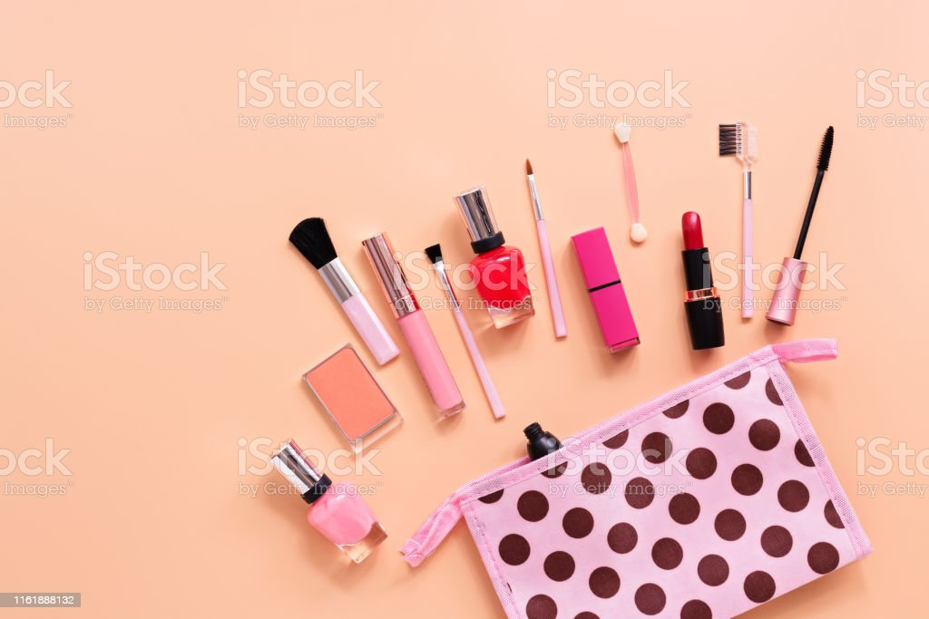 Various women\'s makeup cosmetics on a soft pink background. Cosmetic...