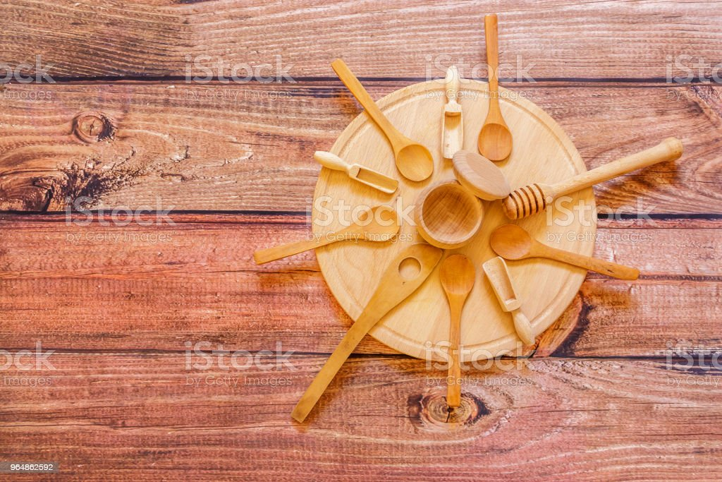 Various wooden kitchen utensils on wooden plate on wooden  table top view royalty-free stock photo