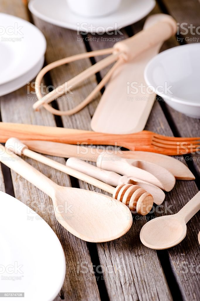 Various wooden spoons among white plates and bowls stock photo