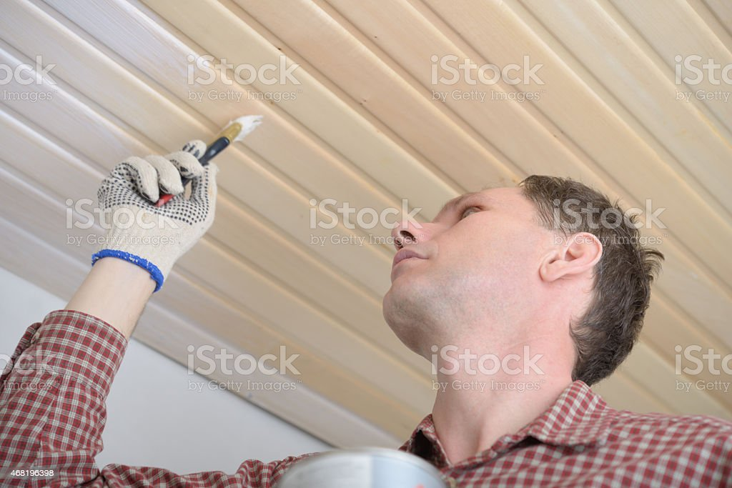 Varnishing a wooden ceiling stock photo
