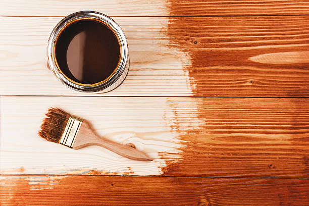 varnishing a wooden shelf - houtbeits stockfoto's en -beelden