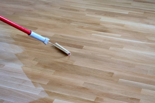 Varnishing Lacquering Parquet Floor Varnishing lacquering an oak parquet floor by paint roller first layer. lacquered stock pictures, royalty-free photos & images