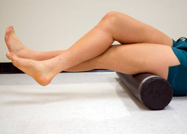 Varsity athlete using a foam roller to release her tight muscles stock photo