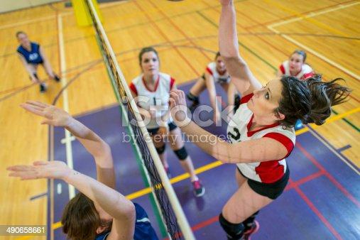Girls having volleyball game indoor