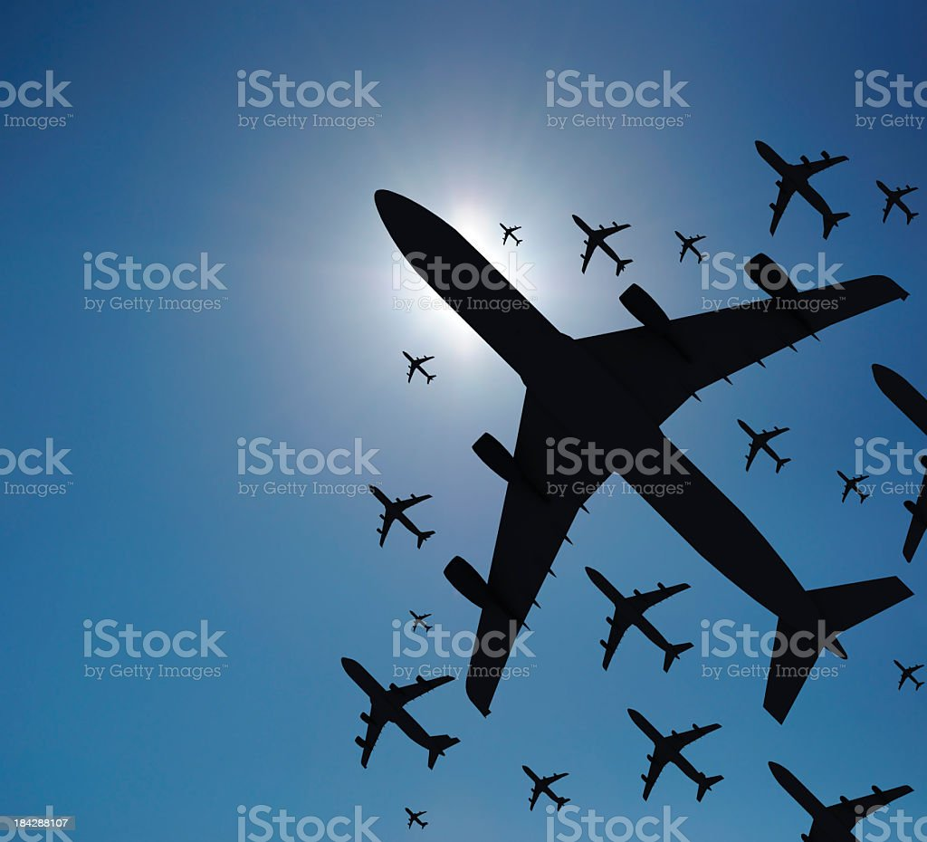Varying sizes of airplane silhouettes set against a blue sky stock photo