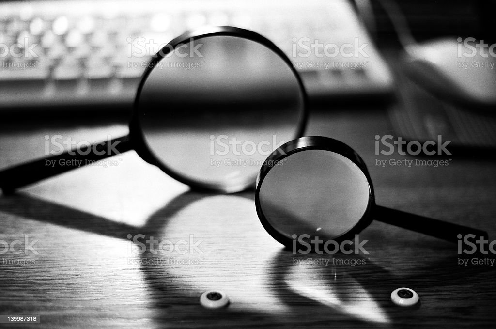 Varying sizes of magnifying lenses near a computer stock photo