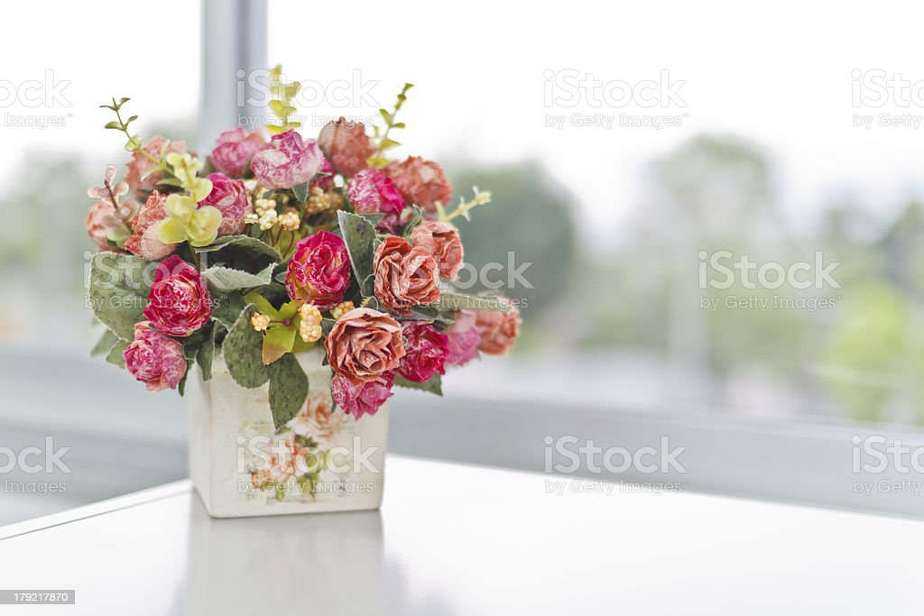 A vase full of pink flowers on a white table stock photo