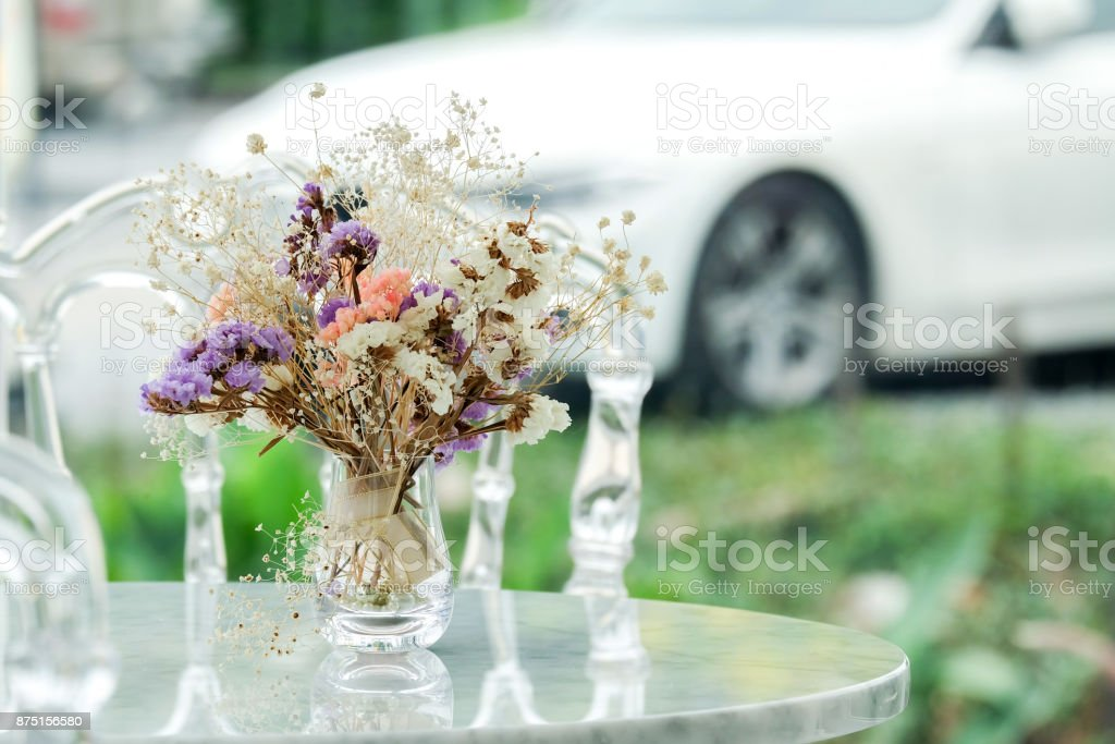 vase glass with beautiful dried flower decorated on a marble table.