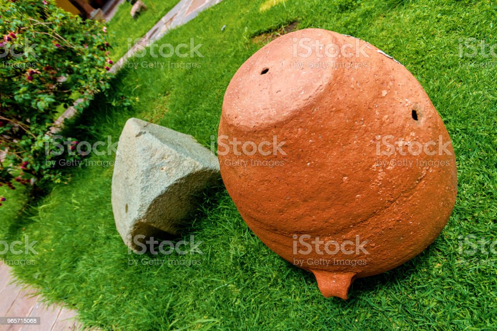 Vase of adobe next to a stone on the lawn of a garden - Royalty-free Adobe - Material Stock Photo