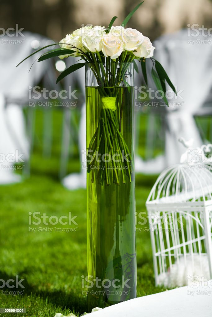Vase of flowers on a green lawn. Decoration for event wedding royalty-free stock photo