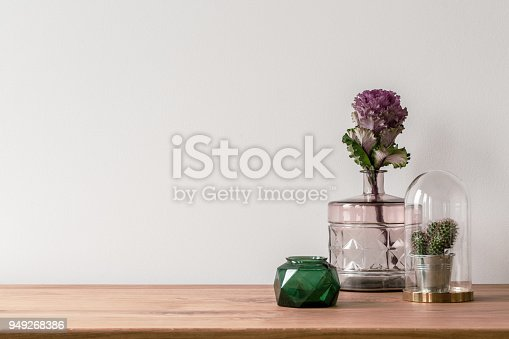 Close-up of a flower in a pink glass vase and a small cactus in a dome on the side of a wooden surface and a empty white background