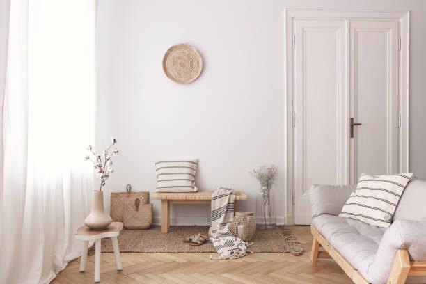 Vase mit Baumwollblume auf Holztisch neben Couch in stilvoller Beige Wohnung – Foto