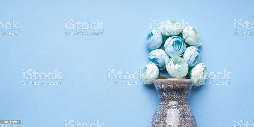 Vase with decorative flowers on blue background royalty-free stock photo