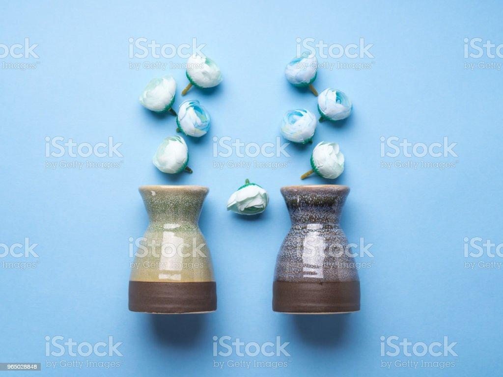 Vase with decorative flowers on blue background royalty-free stock photo