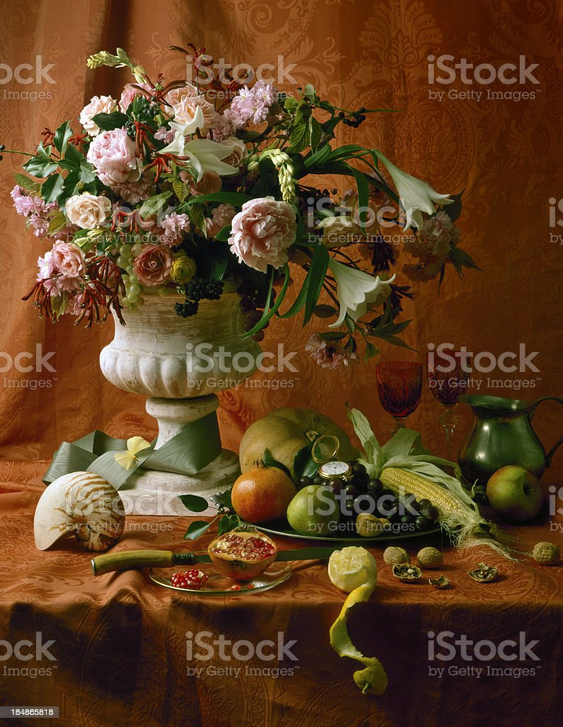vase with peony, pink roses and a bowl of fruit stock photo
