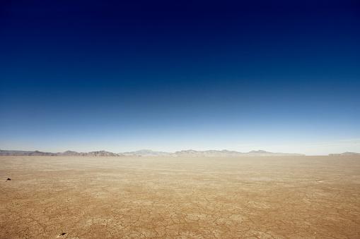 Flat desert scene with mountains at the horizon.