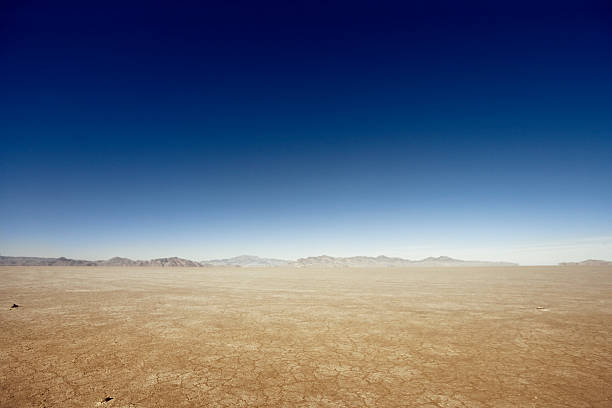 Vast Dry Land Flat desert scene with mountains at the horizon. horizon over land stock pictures, royalty-free photos & images