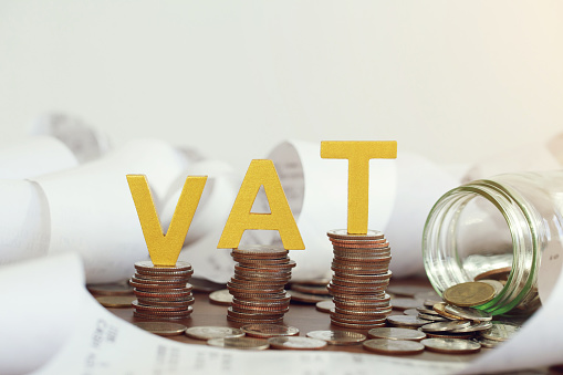 Vat Concept. Word vat put on stacked coins and glass bottles with coins inside on the wooden table. Vat time