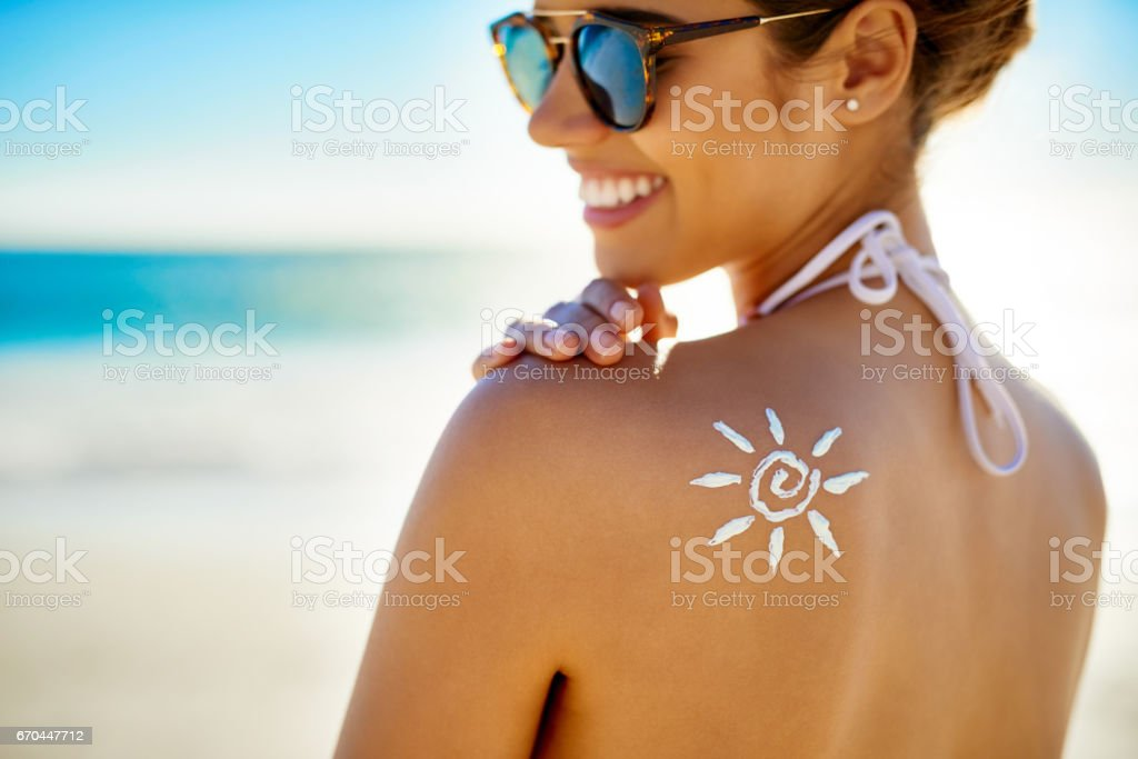 I've all the protection I need against the sun Cropped shot of a young woman posing with suntan lotion on her shoulder 20-29 Years Stock Photo