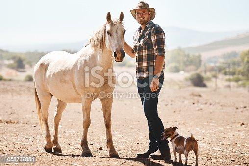 Portrait of a farmer standing with a horse on a ranch