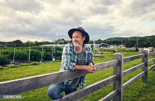 Shot of a mature man standing at a fence on a farm