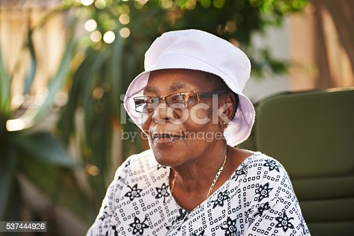 Portrait of a senior woman wearing glasses and a hat outdoors