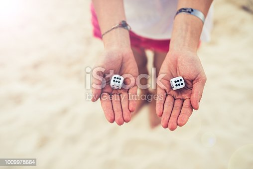 Barefoot Woman on sand beach showing two lucky dices.