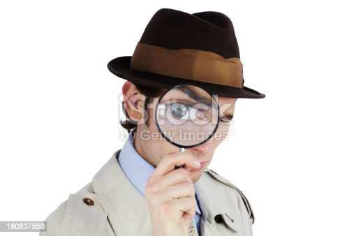 Curious private investigator looking through a magnifying glass against a white background