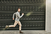 Shot of a young man running in front of a wall