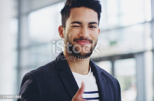 Cropped shot of a young businessman showing winking and showing thumbs up while walking through a modern office