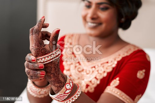 Cropped shot of a beautiful young bride putting on her bracelets in preparation for her wedding