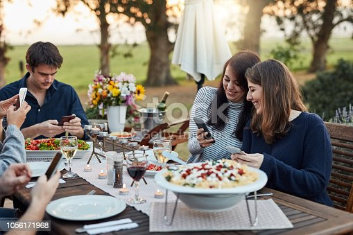 Shot of a group of friends using their cellphones while having a meal together outdoors