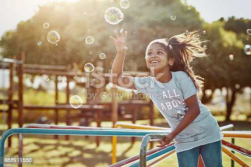 Cropped shot of an adorable little girl playing with bubbles at the park