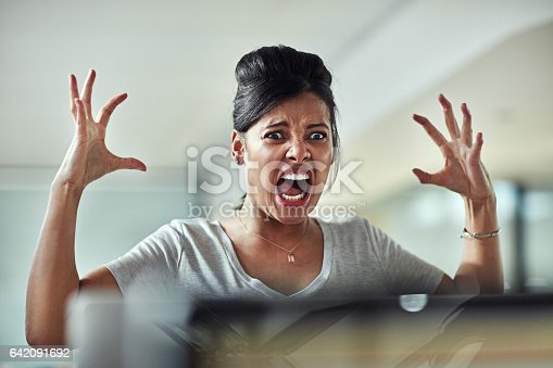 Shot of a frazzled young businesswoman having an outburst in the office