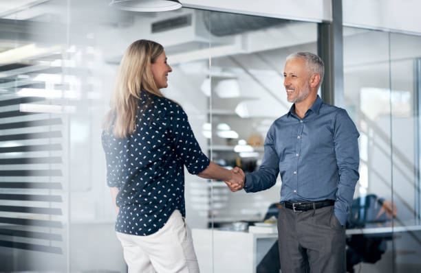 I've heard great things about your company Shot of a businessman and businesswoman shaking hands in a modern office outsourcing stock pictures, royalty-free photos & images