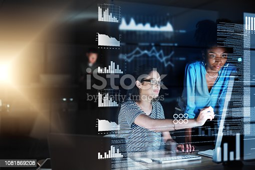Shot of two programmers working together on a computer code at night