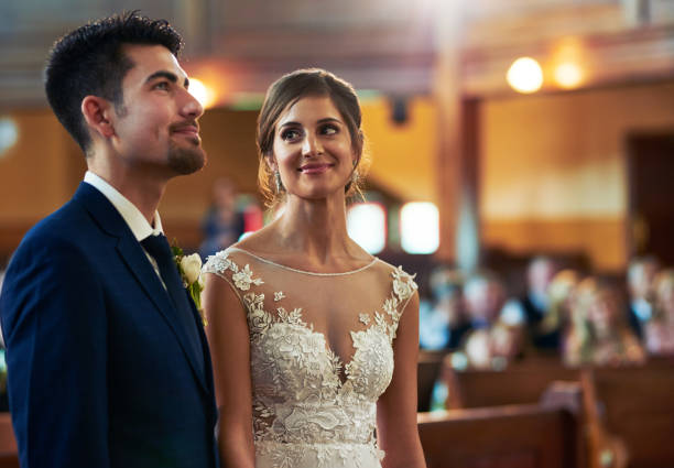 I've never been more sure of anything Shot of a young bride looking fondly at her groom during the wedding ceremony altar stock pictures, royalty-free photos & images