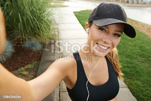 Portrait of a sporty young woman taking selfies while exercising outdoors