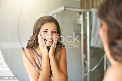 Cropped shot of a attractive young woman admiring her face while standing in front of the bathroom mirror at home