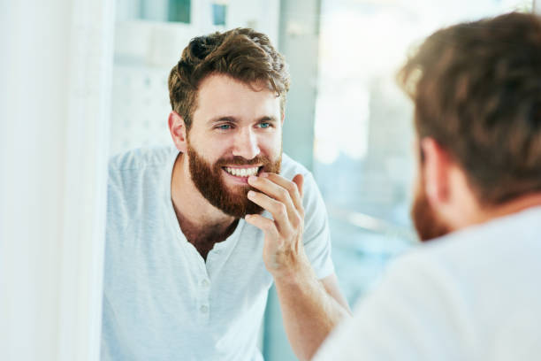 I've never seen a smile more perfect Cropped shot of a handsome young man looking at his teeth in the bathroom mirror teeth stock pictures, royalty-free photos & images