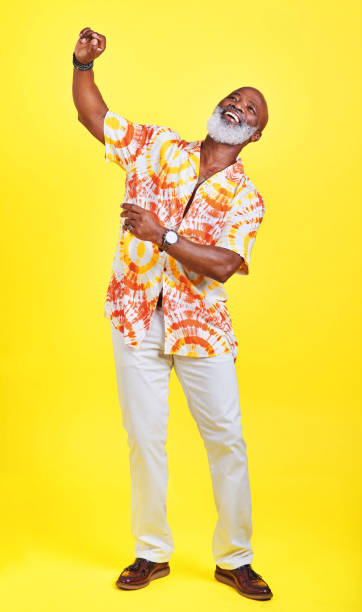 I've still got all the moves Full length shot of a funky and stylish senior man dancing in studio against a yellow background young at heart stock pictures, royalty-free photos & images