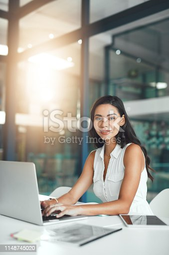 Portrait of a young businesswoman working on a laptop in an office