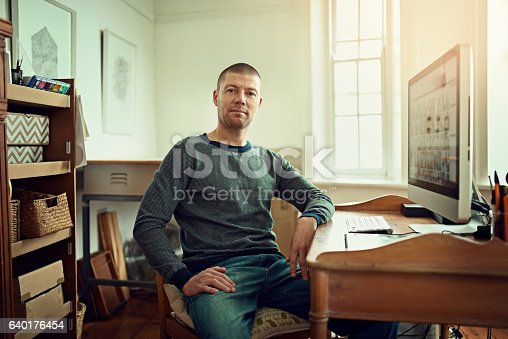 Portrait of a graphic designer working at his desk in a creative office