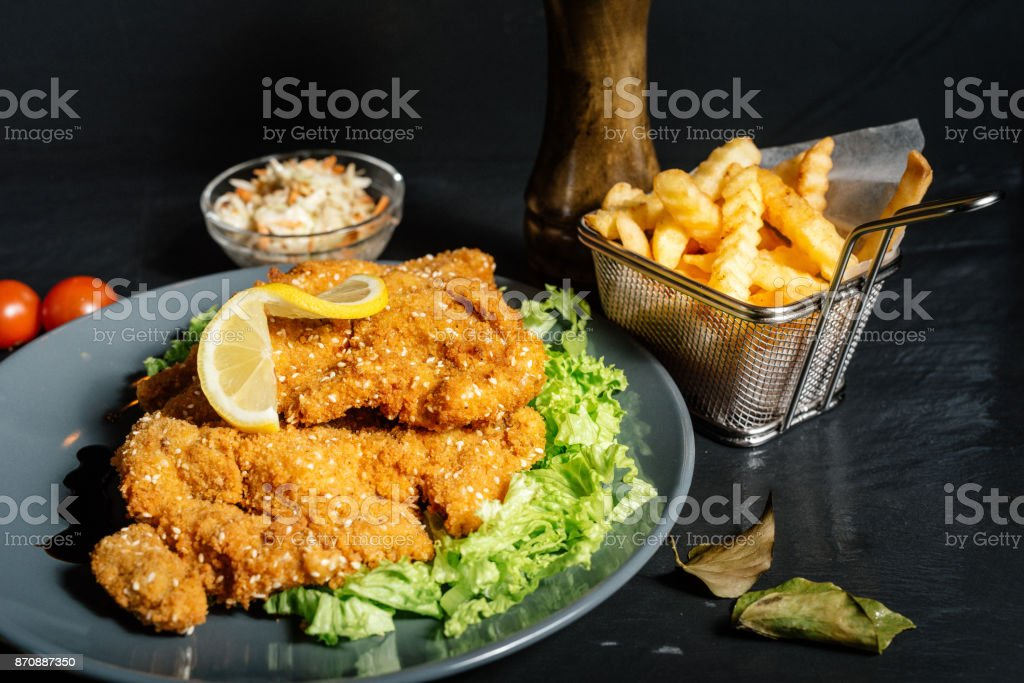 Veal schnitzel as main dish with fries and coleslaw stock photo