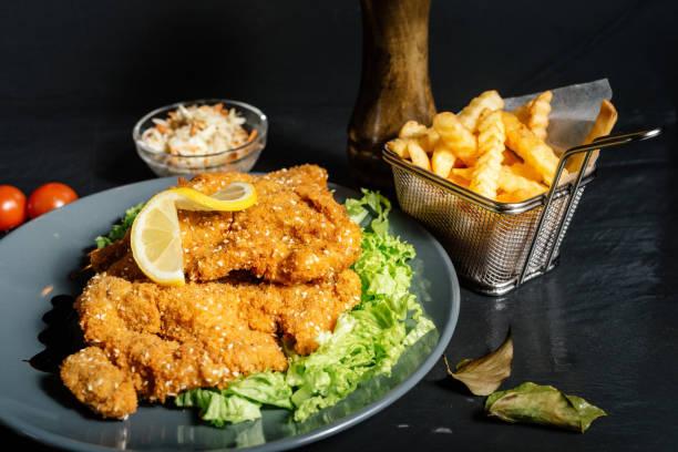kalbsschnitzel als hauptgericht mit pommes frites und krautsalat - schnitzel braten stock-fotos und bilder