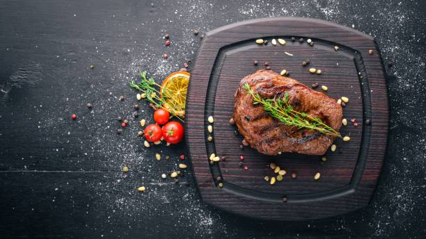 Veal steak with spices on the board. Top view. Free space for text. On a wooden background. stock photo