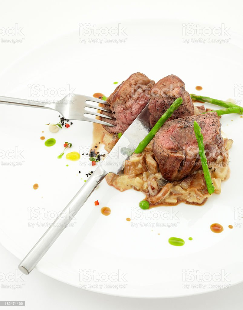Veal steaks with vegetables, served fork and knife. royalty-free stock photo
