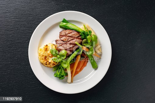 Overhead view of a main course dish of veal tenderloin with seasonal vegetables which include carrots and leeks with a potato gratin and a tomato sauce. Colour, horizontal with some copy space. Shot on location in a restaurant on the island of Moen in Denmark.